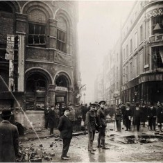 Soldiers & civilians inspecting bomb damage to Wellington Street, Strand, as a result of a Zeppelin night  raid on 13th October 1915. | City of Westminster Archive Centre